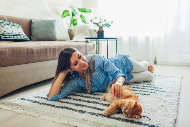 Γυναίκα ξαπλωμένη με γάτα επάνω σε χαλί